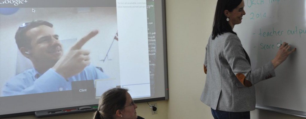 A virtual conference with Clint on a projection screen, and Nicole at a whiteboard.