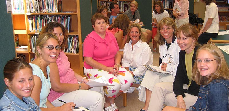 A group of eight smiling teachers working together.