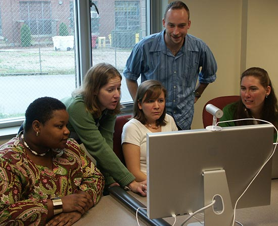 Five New Literacies team members around a computer