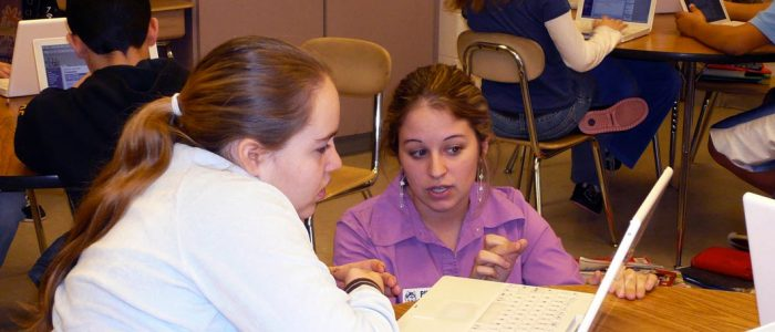A researcher working with a young female student in a classroom.