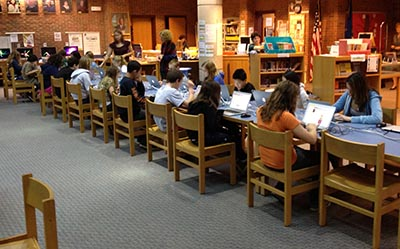 A library setting with many students working at laptops.
