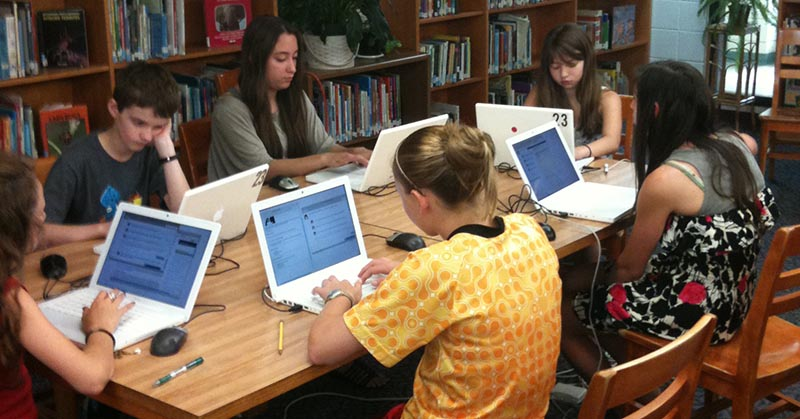 Five students work at laptops in a library
