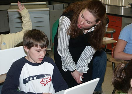 A teacher helps a student at a laptop in a classroom.