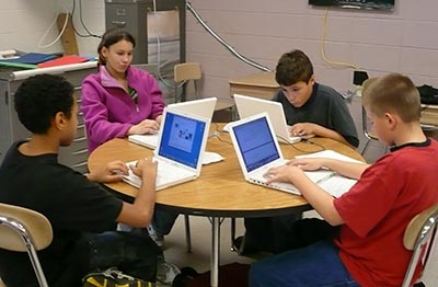 Four young students with laptops around a table